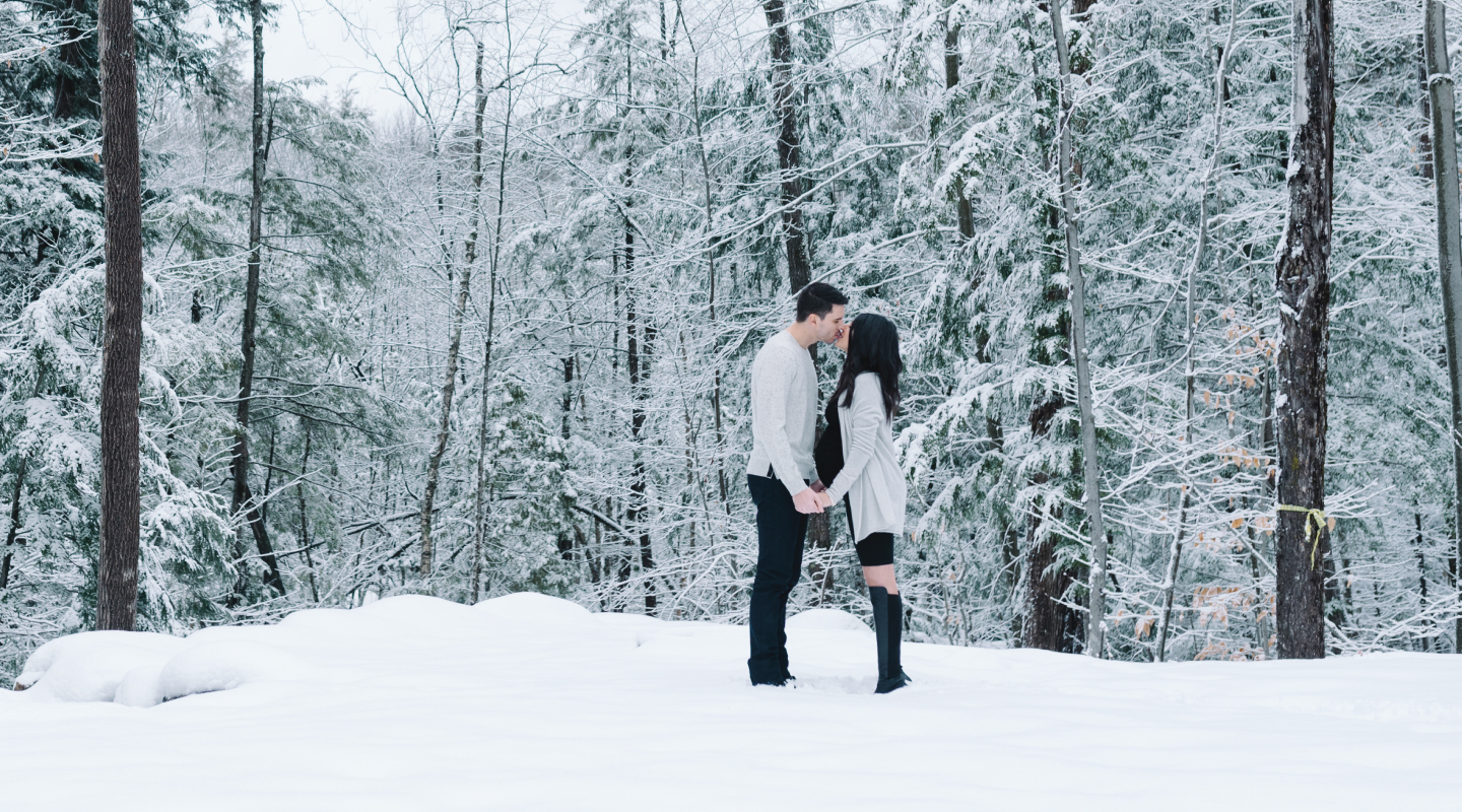 pregnant couple kissing outside in the winter in the snow with a forest behind them
