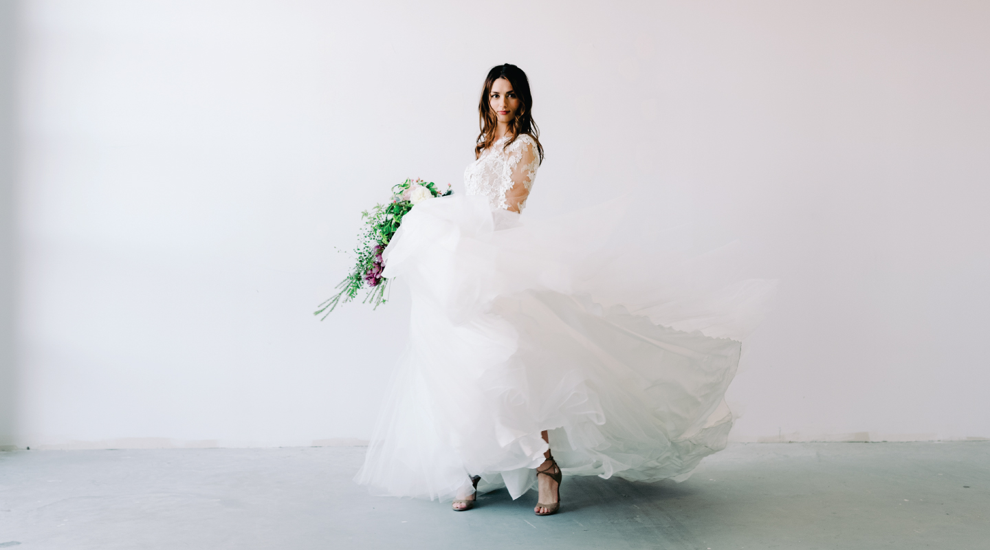 beautiful woman dancing in a wedding dress holding a bouquet of flowers